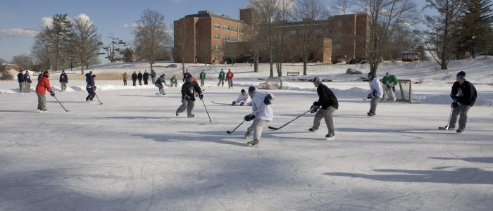 Image of students playing ice hockey on Swan Lake, UConn Storrs Campus.